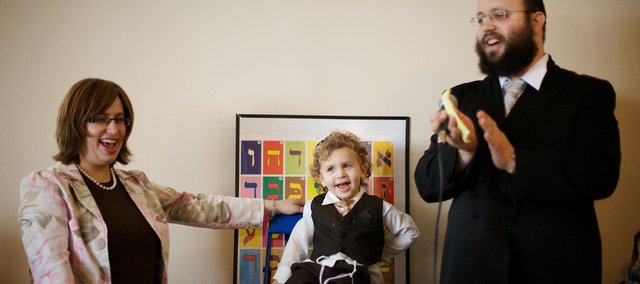 Rabbi Zalman Tiechtel, right, and his wife, Nechama, cheer for their son, Mendel, 3, during his upshernish ceremony March 21 at the Chabad Jewish Center in Lawrence.