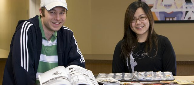 Manga artist Justin Boehle, left, and Mangacandy founder Angela Liu sit among some of the comics Liu's publishing upstart has produced. The Kansas University students rely mostly on comic book conventions to sell their goods.