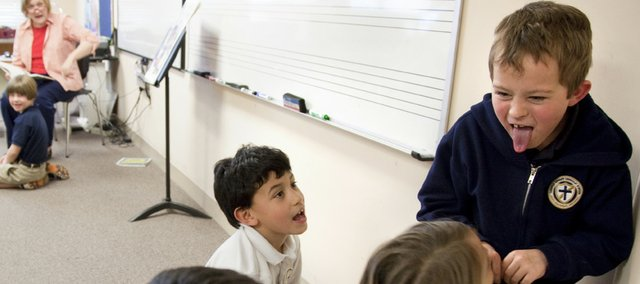 "Playing the part of the wolf, Corpus Christi Catholic School first-grader Andrew Leibold rounds up his sheep as he and other second-graders enact the story of ""Peter and the Wolf"" in Mary Cornwell's music class Wednesday at the school. Private schools like Corpus Christi are expecting a rise in enrollment next year as the public school district faces multimillion-dollar budget cuts."