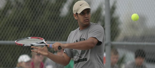 Free State senior Dravid Joseph prepares to return a serve during a singles match against Shawnee Mission North senior Kris Bilyeu, Tuesday, April 6, 2010 at Free State High School.