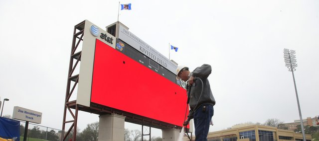 Mike Gardner, who works for American Lift and Sign, a company out of Omaha, Neb., washes down the track at Memorial Stadium Monday, April 5, 2010. The company is installing a new video board with a screen nearly 85 feet wide and 28 feet tall. The new scoreboard is 97 feet tall overall.