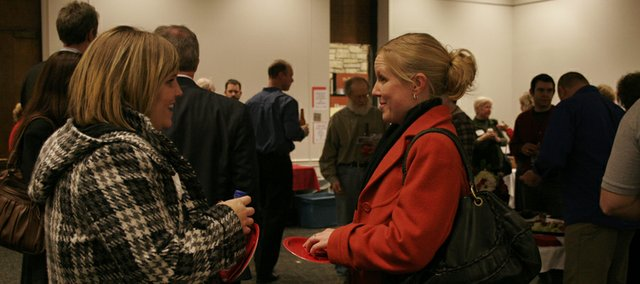 Amanda Diercks and Lana Davis, both of Sunflower Bank, chat during an after-hours mixer Feb. 17 hosted by the Lawrence Chamber of Commerce at the Lawrence Public Library, 707 Vt. Experts say networking is especially important during tough economic times.