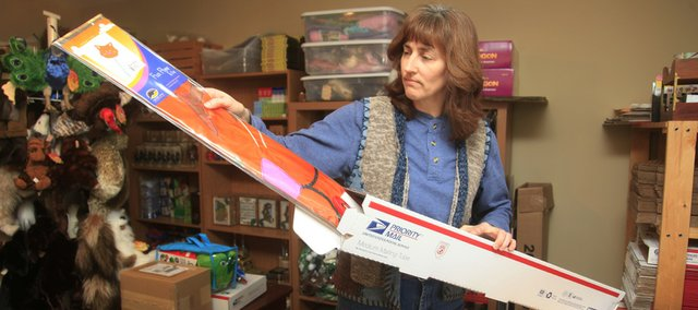 Laura Pate, 45, looks over a product that she and her mother, Barbara Mozingo, sell in their online-based business, Banana Junction Toys, based in Lawrence.