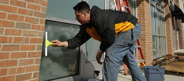 Sergio Perez, a worker with First Management, cleans the exterior windows of a building housing new retail space at the northeast corner of Sixth Street and Wakarusa Drive.
