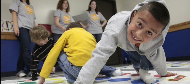 Alex Chavez, 8, gets wound up in a game of Twister Thursday at KU's Burge Union. Volunteers from the KU community are hoping to perform 100,000 hours of community service as a KU provost office initiative and as part of chancellor Bernadette Gray-Little's inauguration.