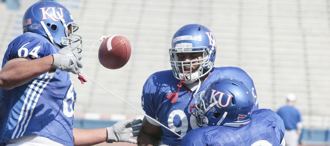 Kansas players Jamal Greene, center, Randell Dent Jr., left, and Patrick Dorsey run through a drill in practice on Friday at Memorial Stadium.