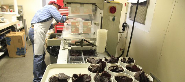 Pat Pyle packages some of the last beef jerky on Thursday at Pyle's Meat in Eudora. Pyle's is closing after 50 years of being in business.