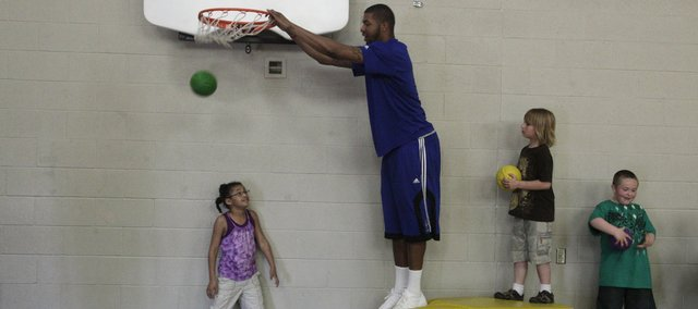 Second-grade student Mercedes Austin, left, gets dunked on by Markieff Morris while Elijah Baum and Xavier Watson, right, wait their turns. Members of the men's basketball team at Kansas University stopped by Sunflower School on Wednesday for a fun and fitness program.