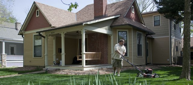 Property owner Dan Schriner mows Thursday at 824 La. The Old West Lawrence home is one of 22 homes on the Spring Parade of Homes, which begins Saturday.