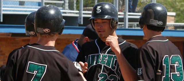 Free State's Cody Kukuk (22) gets congratulated by his teammates after a grand slam. Kukuk smashed three home runs — two grand slams — and Free State hammered Heritage (Ark.), 14-1, on Saturday at Hoglund Ballpark.