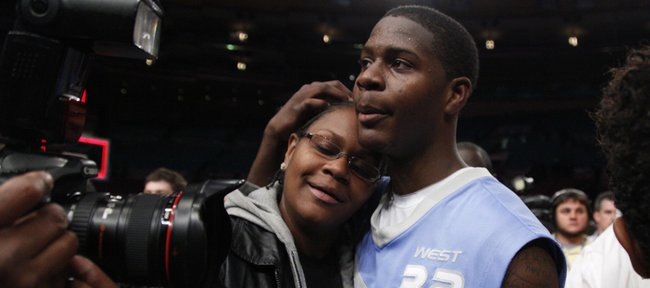 Josh Selby, right, gives his mother, Maeshon Witherspoon, a hug on the court following the Jordan Brand Classic. Selby announced that he would play basketball at Kansas University on Saturday at Madison Square Garden in New York.