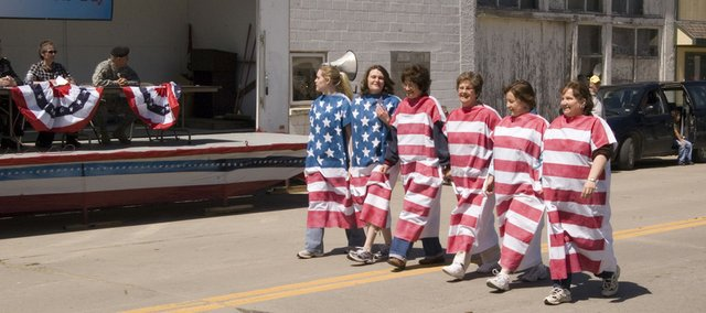 Bank of McLouth employees, from left, Sarah King, Cristie Clark, Alicia Wood, Kathy Scott, Alana Smarker and Cindy Werner march in the McLouth Patriots Day Parade on Saturday.