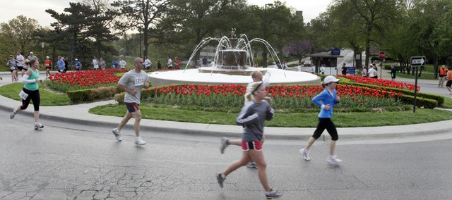 Marathon runners round the Chi Omega fountain on the Kansas University campus in the Lynn Electric Kansas Marathon on Sunday. More than 1,500 runners competed in various races that ran through southwest Lawrence and the KU campus.