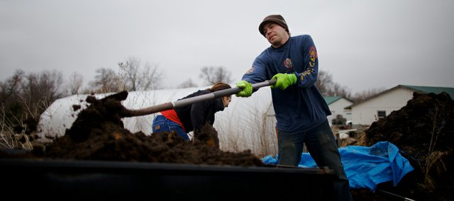 Marc Laning, front, and Audrey Coleman, both of Lawrence, pile compost in a trailer during onion planting March 17 at Spring Creek Farm, south of Baldwin City.