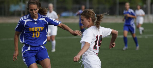 Lawrence High junior Kendyll Severa, right, looks to push the ball past Olathe South's Abby Rhodes on Tuesday at Lawrence High.