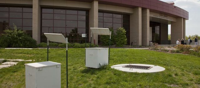 White boxes in front of Ambler Recreation Center hold monitoring equipment used to measure the effectiveness of water collected for the KU rain garden.