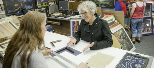 Frame Woods employee Mary Ellen Kriegh, foreground left, helps Robin Gingerich choose some framing options for a family document Thursday. Sales tax collections in the city were down 5 percent for the first three months of the year, as consumers spent less in the sagging economy.