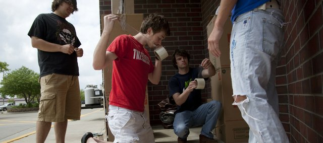"Tau Kappa Epsilon fraternity members, from left, Ryan Ebeling, Overland Park sophomore, John McNeely, Overland Park junior, Joe Winters, Frederick, Md., junior and Austin Grasser, Overland Park sophomore, obscured, work to construct a living quarters made of cardboard boxes Friday outside the Clinton Parkway Hy-Vee. Members of the fraternity plan to live in the box structures for 48 hours, until noon on Sunday, as a part of the ""TKE in a Box"" charity fundraiser. The fraternity is collecting canned goods to be distributed to ECKAN and monetary donations for the Lawrence Community Shelter."