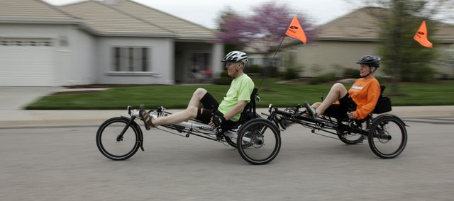 Dr. Charles Yockey and his wife, Nancy, ride their recumbent, tandem tricycle down a residential street. The Yockeys ride as often as they can in the evenings, and usually cover about 20 miles in two hours.