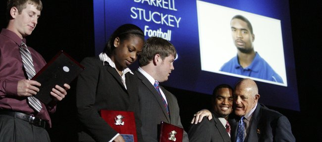 Kansas University athletic director Lew Perkins, right, hugs football player Darrell Stuckey after he was recognized as one of the Senior Athletes of the Year on Monday at the Jayhawk Senior and Scholar Athlete Banquet at Allen Fieldhouse. Also on stage are, from left, baseball player Robby Price, basketball player Danielle McCray and football player Brad Thorson, accepting for Kerry Meier.