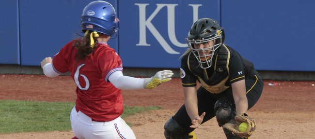 Kansas' Alicia Irwing (6) has no place to go as she slides toward home and waiting Wichita State catcher Heather Gerritse. KU split a doubleheader with the Shockers on Wednesday at Arrocha Ballpark.