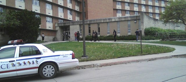 KU Public Safety officers stream into McCollum Hall Friday afternoon to investigate a report of man with a gun who was in the building. Police put the building on lockdown but have also checked at least two locations around Lawrence for the suspect.