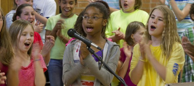 Clapping in rhythm to the music, front from left, Rebeka Drew, Raemona Wilson and Aubin Murphy keep time with the rest of Pinckney School's fifth- and sixth-graders as they perform a selection of students' poems put to music composed by Daniel Musselman, a doctoral student at Kansas University. Murphy's poem was among those featured.