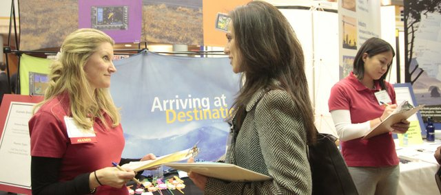 Stacy Walker, college relations recruiter with Garmin, left, talks with Kansas University engineering graduate student Maryam Mahani at the Feb. 11 Engineering and Computer Career Fair at the Kansas Union.