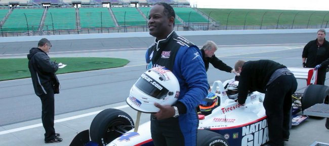 KU football coach Turner Gill poses with the Indy car he caught a ride in on Saturday at the Kansas Speedway in Kansas City, Kan.