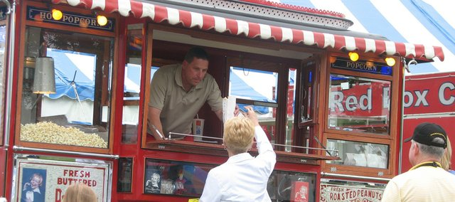 Red Truck Novelties, of Shawnee, serves popcorn to Kansas Sampler Festival attendees Saturday in Leavenworth through a 1929 Ford Model AA popcorn truck.