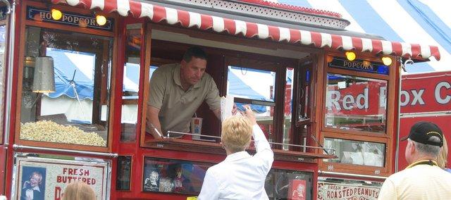 Red Truck Novelties, of Shawnee, serves popcorn to Kansas Sampler Festival attendees Saturday in Leavenworth through a 1929 Ford Model AA popcorn truck.