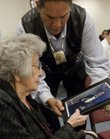 Maria Hinton, 99, receives an autographed photo of Wayne Newton from her grandson Ernie Stevens Jr. on Thursday during a reception at Haskell Indian Nations University. Hinton is the university's oldest living graduate.