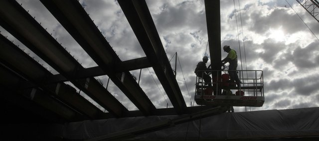 Workers install new beams spanning the Kansas Turnpike's eastbound lanes over U.S. Highway 59 on Thursday in North Lawrence.