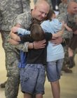 Staff Sgt. Christopher Huslig, of Eudora, hugs three of his children Friday at the Kansas National Guard Armory in Lawrence. Huslig just returned from an eight-month peacekeeping mission in Kosovo and is eager to get on with his civilian life.