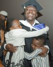 Chief warrant officer Ari Jean-Baptiste is hugged by his children Pria, 9, and Noah, 7, after their father was hooded in a master's degree hooding ceremony Saturday at Kansas University. Jean-Baptiste is one of six soldiers in the Wounded Warrior Educational Initiative at KU who are graduating this weekend.