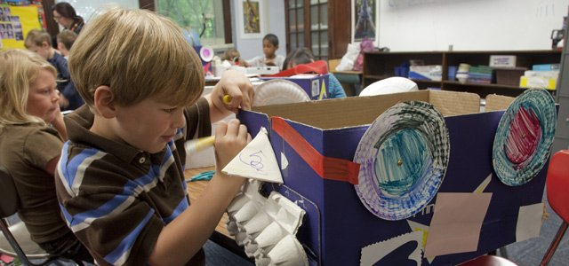 Kindergarten students at Woodland School — like Cole Mies — are creating cardboard art cars for the Art Tougeau parade. concentrates closely on his detail work.