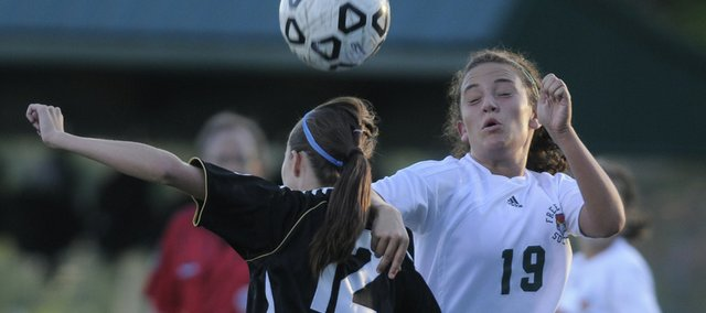 Free State forward Madisyn Warinner fights for control of the ball with Olathe Northwest defender Jessica Parra.