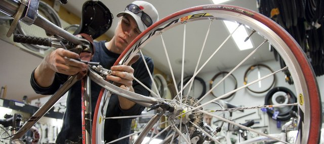 Bike technician Benn Stover works on a customers bike Monday at Cycle Works, 2121 Kasold Drive. The shop is owned by Gary Long, and all of his employees bike to work.