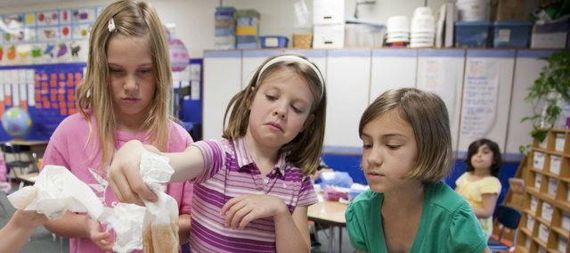 Quail Run first-grader Olivia Ryan, center, pulls a soiled paper towel from a mixture of water, vegetable oil and cocoa mix as her classmates Olivia Ferguson, left, and Patricia Thomas watch Thursday in Mary Pendry's class.