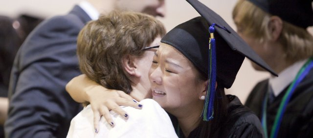 A teary-eyed Jasmine Tse hugs Bishop Seabury Academy secretary Betsy Alford as she and other graduates make their way down the line of faculty members giving hugs and handshakes during the school's stepping-up ceremony after the conferral of degrees Friday at the school. The school graduated 13 students.