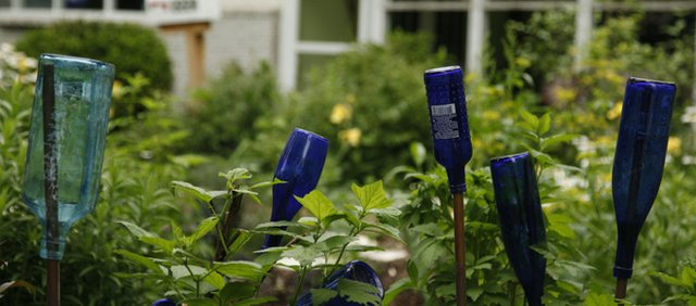 To add a bit of color, Myers has interspersed bottles throughout her rain garden. Rain gardens should be at least 10 feet from homes to allow for adequate drainage from the foundation. Gardens also should drain away from homes and other buildings.