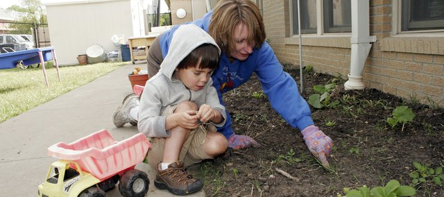 Taj Polonchek, 5, looks for guidance for weeding from teacher Julie McEathron at Hilltop Child Development Center's Meadowlark Classroom's garden. McEathron has incorporated gardening into the classroom for three years, and soon the entire school will have a new garden for its projects.