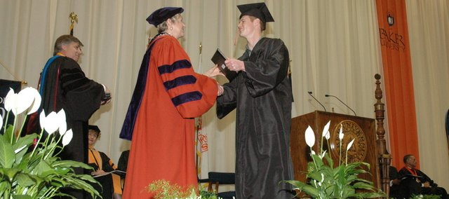 Baker University President Pat Long shakes hands with Matthew James during commencement ceremonies Sunday in Baldwin City. The Class of 2010 arrived at Baker at the same time Long did, four years ago.