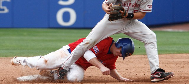 Kansas' Robby Price, bottom slides hard into second base to break up a double play against Oklahoma. OU rallied for a 9-6 victory on Sunday at Hoglund Ballpark.