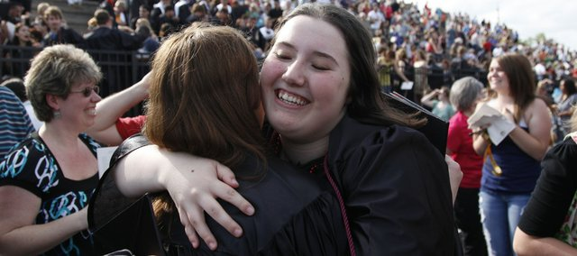 Lawrence High graduate Cassie Brabant, facing, hugs her friend Angele Lund following the LHS commencement ceremony Sunday at the football stadium.