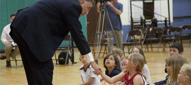 Secretary of State Chris Biggs shakes hands with Woodlawn School first-grader Lakyn Roerich-Putthoff during his visit to the school Tuesday. Biggs also sang and played his guitar and banjo for the students. On the last day of school, he recognized students with good-attendance records.