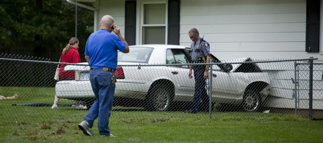 A law enforcement officer and others walk around a car that crashed into the side of a house located at the intersection of 13th Street and Wagon Wheel Road around 11:15 a.m. Tuesday. Witnesses told police that the car was traveling westbound on 13th Street at very high speeds, perhaps in excess of 60 mph. The driver was a 16-year-old Lawrence boy, and he had two 17-year-old passengers in the vehicle. Only minor injuries were reported.