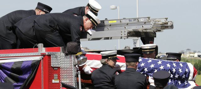 Members of the same crew shift of fallen firefighter of John Glaser lower his casket from a pumper truck after arriving at the Church of the Resurrection on Thursday.