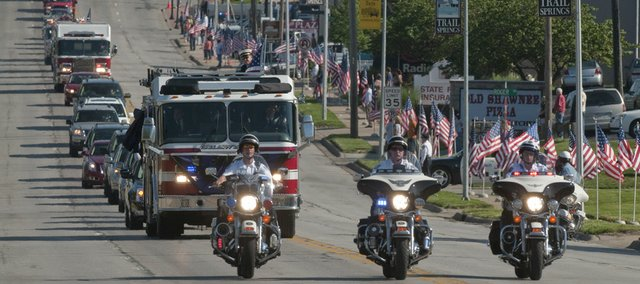 The funeral procession for Shawnee firefighter John Glaser makes its way down Nieman Road on Thursday with a police motorcade.