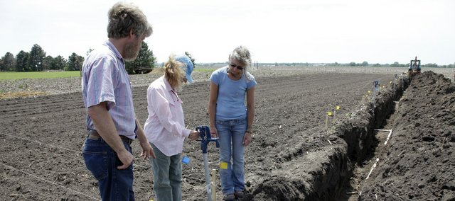 Kelly Kindscher, left, Hillary Loring and Kirsten Bosnak check over one of the new faucets for an irrigation pump. New irrigation pumps are being installed in the section of the Native Medicinal Plant Research Garden just north of Lawrence.